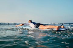 Man surfer swim on surfboard to waves line Royalty Free Stock Photo