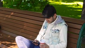 Man surfing in internet via smartphone. And drinking coffee in the park stock footage