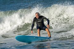 Free Man Surfing On A Blue Surfboard Stock Photography - 202557742