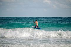 Man sails surfing on the waves in the Caribbean, in Cancun, Mexico. Man surfing with a paddle on the waves in the Caribbean, Cancun, Mexico royalty free stock photos