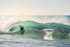 Surfer riding a perfect barrel of a wave at sunset royalty free stock image