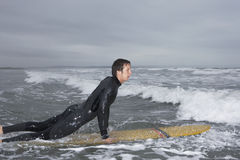 Man Surfing In Water At Beach. Side view of young man surfing in water at beach Royalty Free Stock Images