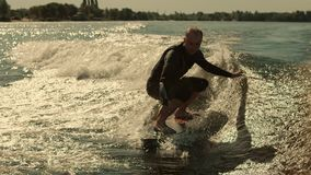 Man surfing on waves in slow motion. Wake surfing rider enjoy waves. Close up of extreme rider on wakesurf board stock video