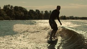 Man surfing on waves. Sportive man surfing on wakeboard in slow motion. Sportsman training wakesurfing at sunset stock video
