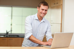 Man surfing the web in the kitchen Royalty Free Stock Image