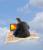 Man surfng internet flying away on magic carpet Royalty Free Stock Images