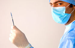 Man surgeon holds a scalpel in an operating room Stock Image