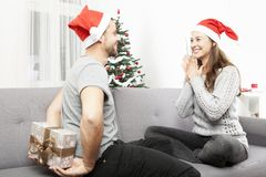 Man surprise girlfriend with christmas gift. Young men surprise girlfriend with gift for christmas with present box behind his back Stock Photo