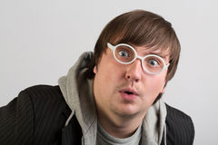 A man with a surprised face. In white round glasses Stock Photos