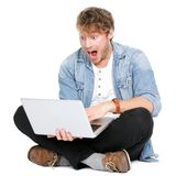 Man surprised with laptop computer. Looking at screen excited and happy in disbelief. Funny image of young Caucasian male student model sitting on floor Stock Photography