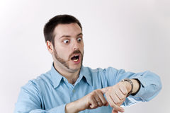 Man surprised, looking at his wrist watch with fea Royalty Free Stock Image