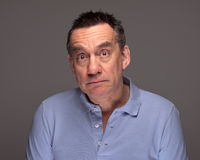Man with Surprised Sad Expression. Handsome Middle Age Man with Surprised Sad Expression on Grey Background Stock Photo