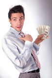Man is surprised to money. Man in a white shirt and a red tie on a white background. The businessman holds money in hands. Hands are lifted upwards and pressed Stock Images