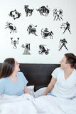 Man and surprised woman in bedroom. Man and surprised women in bedroom surrounded looking up at horoscope zodiac 12 signs. Young couple in bed, domestic Stock Image