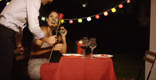 Man surprises his beautiful date with single rose Royalty Free Stock Photo