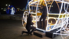 Man surprises his girlfriend with engagement ring at fair in Christmas carriage decoration. Man surprises his girlfriend with engagement ring at fair in a stock video footage