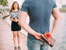 Man surprises his girlfriend by giving out a gift - love and rel Stock Image