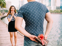 Man surprises his girlfriend by giving out a gift - love and rel Stock Photos