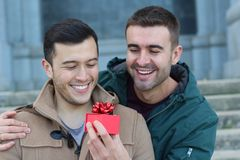 Man surprising his boyfriend with a present royalty free stock photography