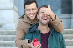 Man surprising his boyfriend with a present royalty free stock photo
