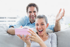 Man surprising his delighted girlfriend with a pink gift on the sofa Stock Images