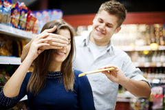 Man surprising his girlfriend. Supermarket: men surprising his girlfriend Royalty Free Stock Photos