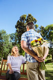 Man surprising his girlfriend with a bouquet in the park Stock Images