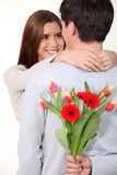 Man surprising his girlfriend with flowers. Man surprising his girlfriend with a bunch of flowers Royalty Free Stock Photography