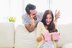 Man surprising his girlfriend with a gift on the couch Stock Photos