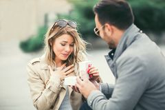 Man surprising his girlfriend with a gift. Stock Photos