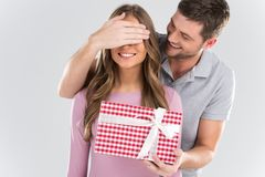 Man surprising his girlfriend with gift on grey background. Stock Image