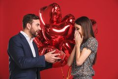 Man surprising his girlfriend with a gift. VAlentines day concept royalty free stock image