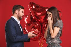 Man surprising his girlfriend with a gift Stock Images