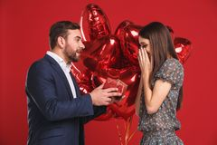 Man surprising his girlfriend with a gift Stock Photo