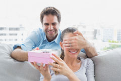 Man surprising his girlfriend with a pink gift on the sofa Stock Photo