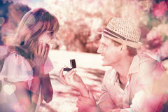 Man surprising his girlfriend with a proposal in the park Stock Photo