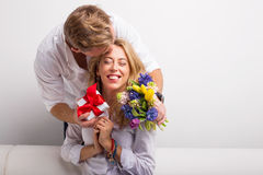 Man surprising his woman with flowers and gift Royalty Free Stock Photos
