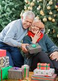 Man Surprising Senior Woman With Christmas Gifts. Happy senior men covering woman's eyes while surprising her with Christmas gifts in store Stock Photos