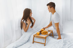 Man surprising woman with breakfast in bed Stock Photography