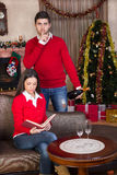 Man surprising woman on Christmas evening. Man with champagne in hand surprising women on Christmas stock images