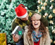 Man In Surprising Woman With Christmas Gift At. Young men in Santa hat covering woman's eyes while surprising her with gift at Christmas store Royalty Free Stock Photos
