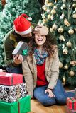 Man Surprising Woman With Christmas Gifts In Store. Young men in Santa hat surprising women with Christmas gifts in store Stock Photography
