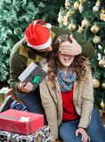 Man Surprising Woman With Christmas Presents In. Young men in Santa hat surprising women with Christmas presents in store Stock Photography