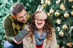 Man Surprising Woman With Gift In Christmas Store. Young men covering woman's eyes while surprising her with gift in Christmas store Stock Photo