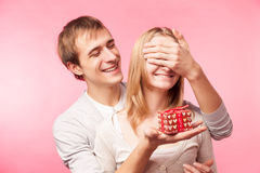 Man surprising woman with present over pink Stock Photography