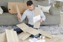 Free Man Surrounded By Pieces Flat Pack Furniture Stock Photo - 100426690