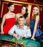 Man surrounded by girls plays roulette Stock Photo