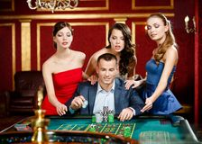 Man surrounded by pretty girls gambles roulette stock image