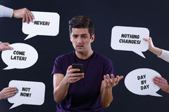 Man surrounded by speech bubbles. Hesitant young men surrounded by speech bubbles with comments Royalty Free Stock Image