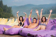 Man is surrounded by two women sitting on a cushioned lounger with his hands raised up and looking to the camera. On the blurred background of forests and hills royalty free stock images